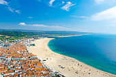 Watercolor drawing of panoramic view of Nazare town in summer, mountain landscape with dense greenery background, Nazare coastline with white sand and blue azure water of the Atlantic Ocean, Portugal