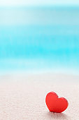 Red heart on sandy sea beach, love summer and relaxation concept.