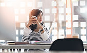 Beautiful asian woman have a coffee break during work.