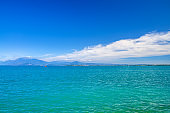 Garda Lake azure turquoise water surface with view of Monte Baldo mountain range and Sirmione peninsula, blue sky white clouds background, Desenzano del Garda town, Lombardy, Northern Italy