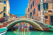 Bridge across narrow water canal in Venice with moored boats between old colorful buildings with balconies and brick walls, blue sky, Veneto Region, Northern Italy. Typical Venetian cityscape