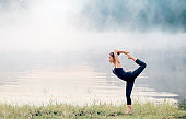 Young beautiful asian woman doing yoga practice on park.