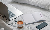 Work from home concept wiht laptop and supplise on white sheets in bed room.