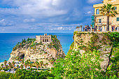 Tropea: people tourists on observation deck view platform Belvedere Piazza del Cannone are looking at Monastery Sanctuary church