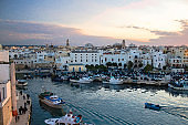 Watercolor drawing of boats in bay harbour of a seaside town Monopoli view from Castle of Carlo V, Puglia Apulia region, Southern Italy