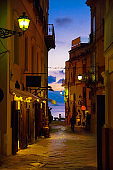 Watercolor drawing of Night evening streets with bright lanterns lamps on buildings with balconies, silhouette of walking man and colorful sky with clouds, Tropea town, Calabria, Southern Italy