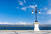 Watercolor drawing of Street lamp lights with bolls on quay waterfront promenade Lungomare Falcomata, Strait of Messina and Sicilia island background, Reggio di Calabria, Southern Italy