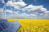 Renewable or green energy concept with wind turbines solar panels and yellow raps field on blue sky with clouds