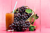 Glass of juice. Natural grape juice. pink background