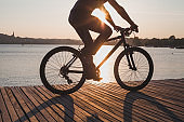 man riding bicycle at sunset, cycling in summer, silhouette of cyclist