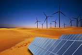 Renewable energy in desert sand dunes at sunset concept with solar panels and wind turbines