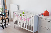 white baby bed crib in child room interior at home