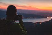 photographer taking photo of night city landscape, travel photography