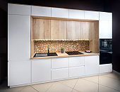 Luxury modern fitted flat design kitchen with surface behind the countertop decorated with wall cross section of tree trunks of cut tree logs, trunks placed together for interior decoration.