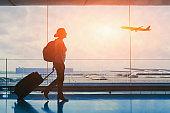 tourist travel to international airport terminal, silhouette of woman passenger