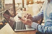 hands holding smartphone in cafe, banking online, freelancer