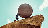 Man wears business suit and pushes big rock up a hill