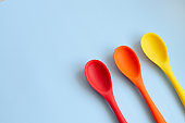 Flat lay of bright multi-colored spoons on a blue background.