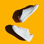 White sneakers on an orange background with hard shadows.