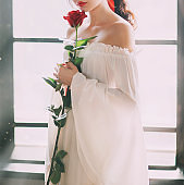 Mysterious silhouette young medieval princess. White luxury vintage sexy dress. bare shoulder. Red rose in hands. backdrop sun light in window. Fantasy portrait no face bride wedding renaissance style
