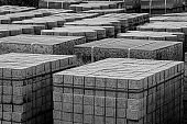Black and white photo of piles of construction material at a construction site