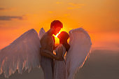 Mysterious dark silhouette two angles meet at sunset hug. Lovers muscular man and tender woman marry in heaven. concept love fidelity. warm color orange sky red sun light sun. Carnival costume wings