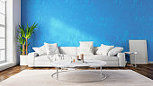 Interior of modern living room with white fabric sofa over blue wall