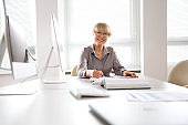 Portrait of mature business woman looking at camera at workplace in an office