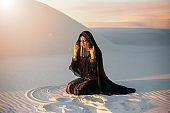 A mysterious woman in a black long dress sits in the desert. Luxurious clothes, gold accessories hide the face. Oriental beauty fashion model. Sand dunes background, orange sunset . Art Fantasy photo