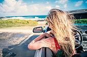 Blond hair woman inside convertible car contemplating seascape