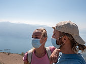 Couple hiking with protective mask against coronavirus