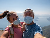 Couple hiking during coronavirus crisis wearing protective mask