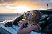 Blond hair woman inside convertible car contemplating seascape at sunset