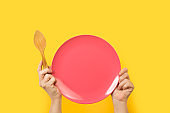 Woman holding a pink plate with both hands on a yellow background