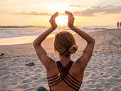 Healthy young woman exercising yoga outdoors on the beach at sunset catching the sun with hands