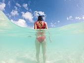Underwater shot of woman standing on beach, looking up