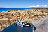 Drone view of young woman sitting on car arms open enjoying road trip