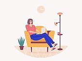 Woman sitting on the sofa and working on the laptop, freelancer home workplace.