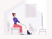 Girl watching television sitting in armchair, at home with cat.