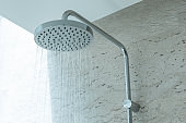 Fresh shower with water drops splashing. Faucet in modern bathroom.