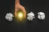 Female hand holding light bulb on black background. New idea concept