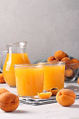 Apricot juice with pulp in two glasses and a jug on a gray background, Closeup