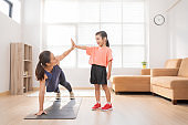 Asian mother and daughter Exercising at home They are having fun together