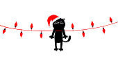 Cute cat in red Santa hat hanging on Christmas lights. Red lightbulb glowing garland. Colorful string fairy light set. Cone shape. Holiday festive xmas decoration. Flat design. White background.