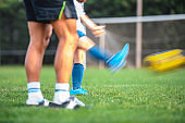 Blurred Motion of Coach and Young Footballer Kicking Ball