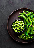 Green peas in  bowl with fresh pods on the black concrete background, top view or flat lay