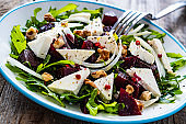 Beetroot salad with goat cheese on wooden background