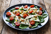 Fresh salad - blue cheese, cherry tomatoes, spinach, walnuts on wooden background