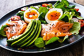 Smoked salmon with boiled eggs, avocado and vegetables on wooden table