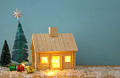 Image of christmas tree and wooden house with light through the window, over snowy table.